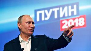 Vladimir Putin pitää puhetta ja osoittaa vasemman kätensä etusormella jotakin.