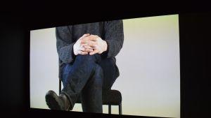mies istuu jalat ristissä