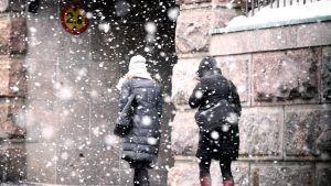 Jalankulkijoita lumisateisessa Helsingissä.