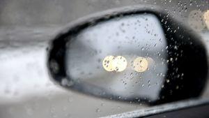 Vettä ja räntää auton ikkunassa ja sivupeilissä.