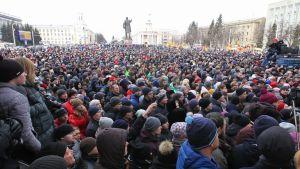 Hallintorakennusten ympäröimä aukio on täynnä ihmisiä. Aukion keskellä näyttää olevan Leninin patsas, joka osoittaa kaukaisuuteen.