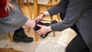 Kotihoitaja auttaa vanhukselta kengän jalasta.