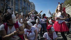 Presidentti Emmanuel Macronin vastainen mielenilmaus Pariisissa 19. huhtikuu 2018. Nuorilla on valkoisia naamioita kasvojen edessä.