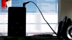 IPod soittaa musiikkia, taustalla iTunesin musiikkikauppa netissä. Suomessa digitaalisen myynnin osuus musiikin kokonaismarkkinoista on 20 prosenttia, kun esimerkiksi Yhdysvalloissa ja Ruotsissa jo puolet äänitteiden tuotoista tulevat digitaalisesta myynnistä.