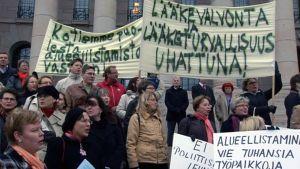 Lääkelaitoksen työntekijät pitämässä mielenosoitusta eduskuntatalon portailla