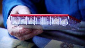 Lääkedosetti eli lääkeannostelija vanhuksen kädessä.
