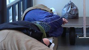 Asunnottomat lepäävät penkillä.