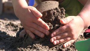 Lapsen kädet tekemässä hiekkakakkua