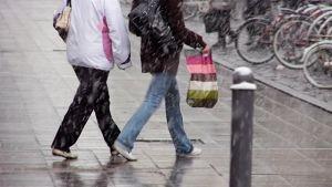 Kaksi naista kävelee kadulla räntäsateessa.
