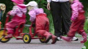 Lapsia ja hoitaja päiväkodin pihamaalla.