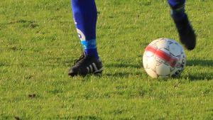 Kuvassa jalkapalloilijan jalat ja jalkapallo.