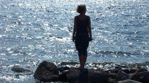 Naisen silhuetti merta vasten.