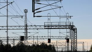 Kuvassa sadan sähköjohtimia Kokkolan ratapihan yllä. Punaiset valot palavat junille.