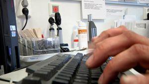 Lääkärin kädet tietokoneen näppäimistöllä vastaanottohuoneessa.