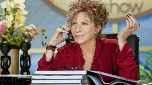 Barbra Streisand puhuu kännykkään ison työpöydän ääressä. Hän tuijottaa kauas eteensä.