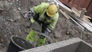 Rakennusmies levittää laastia työmaalla