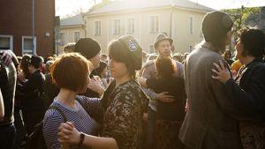Pareja tanssii kadulla Vallilassa auringonpaisteessa.