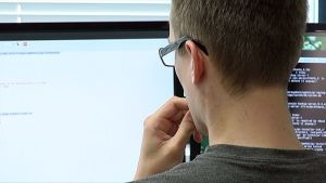 Työntekijä katsoo tietokonemonitoria.