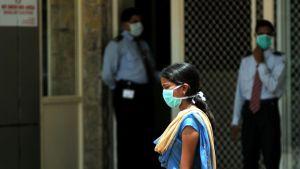 Ihmiset suojasivat kasvonsa hengityssuojilla St. Philomenan sairaalassa, Intian Bangaloressa, elokuussa 2009. Kuvanottopäivänä sairaalassa menehtyi sikainfluenssaan kaupungin ensimmäinen taudin uhri.