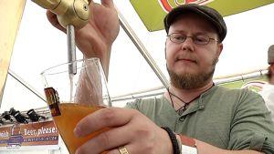 Fiskarsin panimon yrittäjä Jari Leinonen kaataa olutta hanasta Suuret Oluet - Pienet Panimot -festivaalilla.