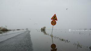 Vettä tiellä, liikennemerkki vinossa pellonlaidalla.