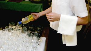 Tarjoilija kaatamassa viiniä laseihin.