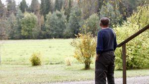 Mies katsoo portailta pellolle.