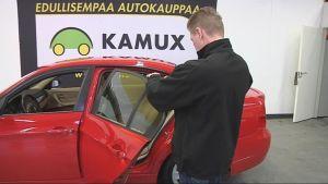 Automyyjä ottaa kuvan henkilöautosta autohallissa.