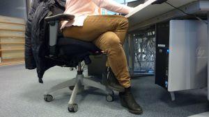 Tuulia Thynell istuu työtuolissa jalat toistensa ympärille kietoutuneina.