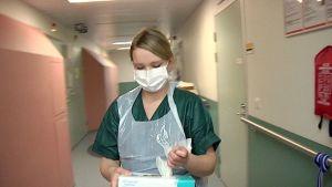 Sairaanhoitaja suojautunut norovirusta vastaan Armilan sairaalassa.