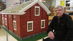 Kuvassa Hannu Virkkala rakentamansa kotitalopienoismallinsakanssa.