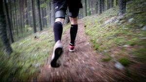 Mies juoksee metsässä.