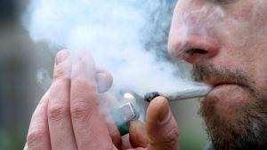Mies polttaa marihuanaa.