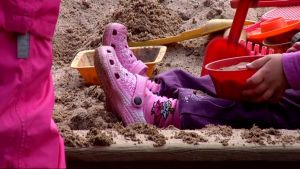 Lapsi istuu hiekkalaatikolla.