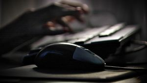 Henkilö kirjoittaa tietokoneen näppäimistöllä. Tietokoneen hiiri kuvan etualalla.