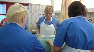 Sairaanhoitajat nostavat potilasta.