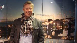 Kokki Jyrki Sukula poseeraa Kuokkalan silta -aiheisen ikkunan edessä.