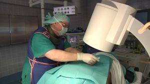 Lääkäri pistää potilasta leikkaussalissa.