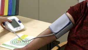 Naiselta mitataan verenpainetta.