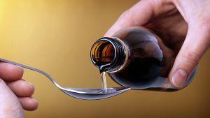 Yskänlääkettä kaadetaan pullosta lusikkaan.