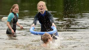Uimakouluopettaja Pinja Vähätiitto leikkii lasten kanssa haukihippaa vedessä. Taustalla Karoliina Ripatti.