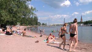 Kirjurinluodon ranta, auringossa paistattelevia ihmisiä