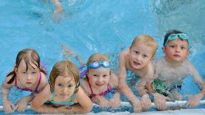 Lapsia uima-altaan reunalla uimakoulussa.