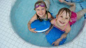 Kaksi tyttöä uima-altaassa.
