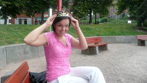Tangokuningatar Maria Tyyster sovittaa kruunua päähänsä puistonpenkillä istuen