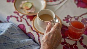 Vanhus juo kahviaan. Mehulasi ja voileipälautanen ovat myös pöydällä.