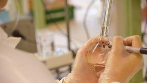 Tutkija kirjoittaa laboratoriopullon kylkeen tussilla.