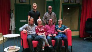 Näyttelijät istuvat sohvalla teatterinäyttämöllä
