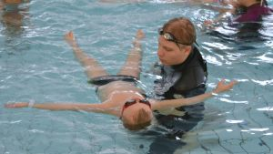 Uimakoulun opettaja opettaa koululaista kellumaan selällään.
