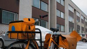 Postinjakajan pyörä kerrostalon pihalla.